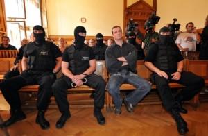 Budapest, 2009. szeptember 16. A három hónapja terrorcselekményekkel és országgyûlési képviselõk elleni támadásokkal meggyanúsított, és elõzetes letartóztatásban lévõ Budaházy György kommandósok között ülve hallgatja az ítélet indoklását. Egy év - három évre felfüggesztett - börtönbüntetésre ítélte az alkotmányos rend erõszakos megváltoztatásának elõkészülete miatt Budaházy Györgyöt a Fõvárosi Bíróság elsõ fokon. Korábban ebben az ügyben elsõ fokon felmentették a vádlottat, ám a Fõvárosi Ítélõtábla azt a döntést hatályon kívül helyezte és új elsõfokú eljárásra utasított. MTI Fotó: Kovács Tamás