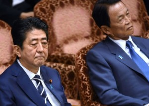 Japan's Prime Minister Shinzo Abe (L) and Deputy Prime Minister Taro Aso (R) attend a budget dommittee meeting in the Upper House at parliament in Tokyo on July 25, 2017, as Abe and other relevant ministers were expected to face more questioning over issues over a suspected scandal. For months Abe has been dogged by scandals, most recently claims he showed favouritism to a friend in a business deal, an accusation he denies. / AFP PHOTO / Kazuhiro NOGI