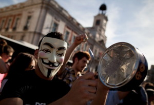 MADRID, SPAIN - MAY 15:  A demonstrator with Spain's Indignant movement wearing a Guy Fawkes mask hits a biscuit tin during a rally at Puerta del Sol on May 15, 2012 in Madrid, Spain. Spain's Indignant movement has prepared events across Spain to mark the first anniversary of their movement, formed to protest against corruption in politics, the economic crisis and the high unemployment rate. The movement's anniversary coincides with Madrid's regional festivities.  (Photo by Pablo Blazquez Dominguez/Getty Images)
