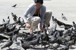 2010-06-14 AMSTERDAM - A tourist at the Dam square between the pigeons. ANP XTRA LEX VAN LIESHOUT