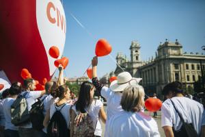 """Szolidaritási akció a Parlamentnél a """"Stop Soros"""" törvénycsomag ellen   Résztvevők egy szív alakú piros léggömb előtt az Amnesty International (AI) """"Stop Soros"""" törvénycsomag ellen tartott szolidaritási akcióján a Parlament előtti Kossuth téren 2018. június 4-én. A képviselők június 5-én folytatják le az egyes törvényeknek a jogellenes bevándorlás elleni intézkedésekkel kapcsolatos módosításáról szóló törvényjavaslat, azaz a """"Stop Soros"""" vitáját. Fotó: Horváth Péter Gyula"""